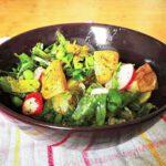 Kartoffelsalat mit grünem Spargel, Radieschen, Erbsen und Rucola in Schüssel