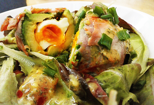 Pochiertes Ei mit Avocado und Bacon auf Salat mit Senfsoße