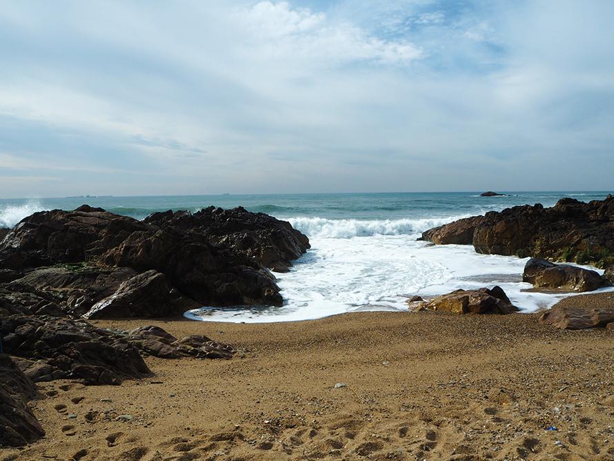 Strand mit Felsen und Wellen